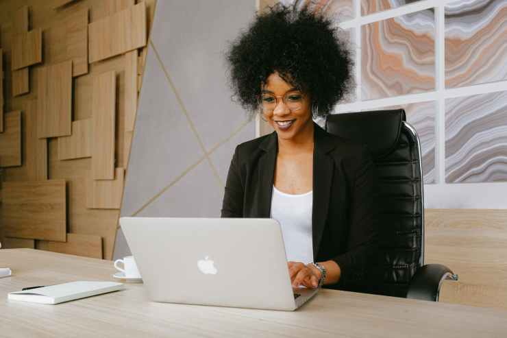 woman in black blazer sitting by the table while using macbook