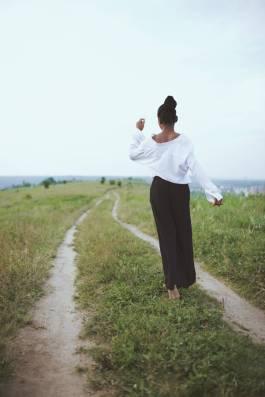 photo of woman walking on grass